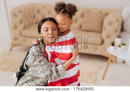 Finally here with you. Sentimental tender young woman looking moved by her daughters greetings and hugging her tightly after returning home