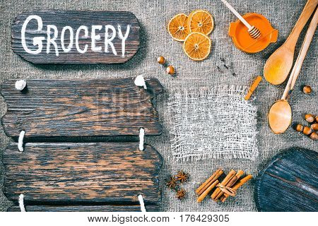 Dark wood boards as frames on burlap background with honey, nuts and aromatic spices. Wooden signboard with text 'Grocery' as title bar. Rustic style template for food and drink industry
