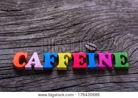 word caffeine and coffee beans on old wooden table