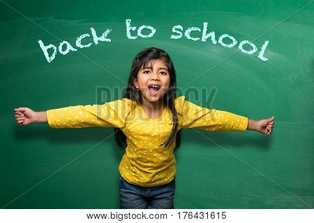 Indian school kid girl in hand stretched pose over green chalkboard or chalk board background, indian boy standing over green chalkboard background in the school with doodles -  back to school concept