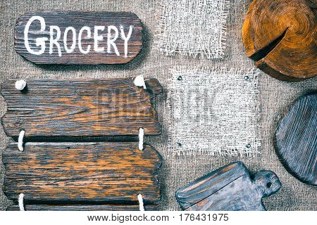 Dark wood boards, wood slice and burlap pieces as frames on burlap background. Wooden signboard with text 'Grocery' as title bar. Rustic style template for food and drink industry