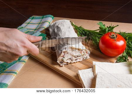 Woman's Hand With Knife In It Cutting Pita Bread Or Lavash Roll With Cottage Cheese Or Curd, Chicken
