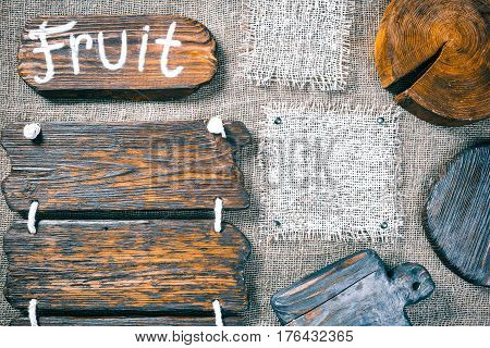 Dark wood boards, wood slice and burlap pieces as frames on burlap background. Wooden signboard with text 'Fruit' as title bar. Rustic style template for food and drink industry