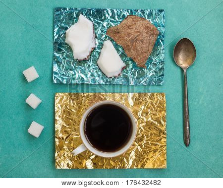 Pieces of coconut and a cup of coffee on stands made of yellow and turquoise foil on a wooden surface