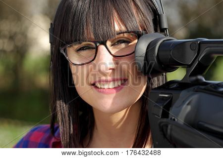 a pretty young brunette girl with a professional camcorder outdoor