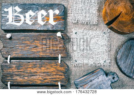 Dark wood boards, wood slice and burlap pieces as frames on burlap background. Wooden signboard with text 'Beer' as title bar. Rustic style template for food and drink industry