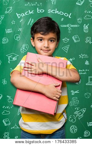 Studious indian school kid holding big book over green chalkboard background with doodles