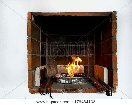 Single use barbecue with flaming coals in a summer terrace