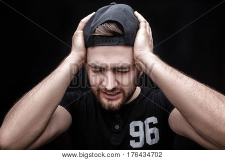 Frustrated young brunette man in black shirt with headache on black background. terrible migraine