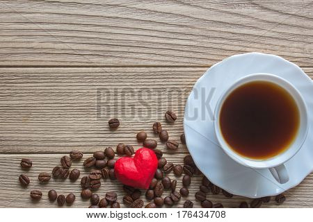 heart condom and a cup of coffee. coffee beans on old wooden table