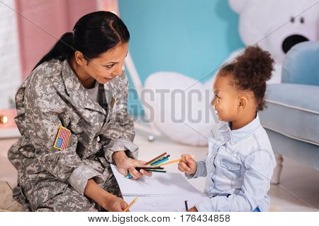 What do you prefer. Lovely emotional cheerful mother asking her daughter about her preferences while spending time at home and playing in her room together