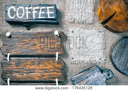 Dark wood boards, wood slice and burlap pieces as frames on burlap background. Wooden signboard with text 'Coffee' as title bar. Rustic style template for food and drink industry