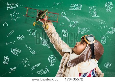 Happy Indian or asian boy kid playing with toy metal airplane against green chalk board with doodles drawn everywhere in the background - Kid and flying or ambition concept