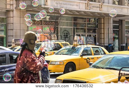 NEW YORK CITY - 30 MARCH 2015: unidentified vendor blowing soap bubbles on the streets of Manhattan with yellow taxi cabs - Everyday life on the cultural and financial capital of the world