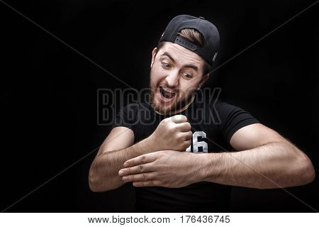 portrait of young man in black shirt and cap on a black background makes the hand trick