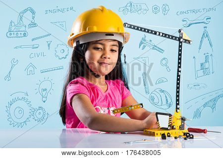 cute indian baby girl playing with toy crane wearing yellow construction hat or hard hat, childhood and education concept