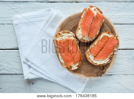 Top view at sandwiches with smoked salmon and cream-cheese on a white wooden table