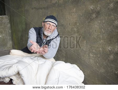 Mature homeless man begging outdoors, sitting in an old blanket
