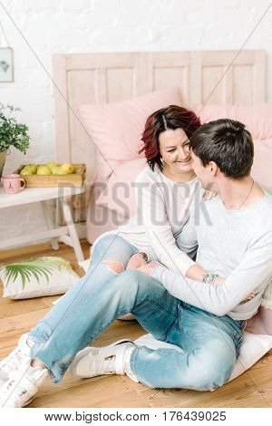 In the big bedroom near the bed a couple in jeans is sitting on the floor