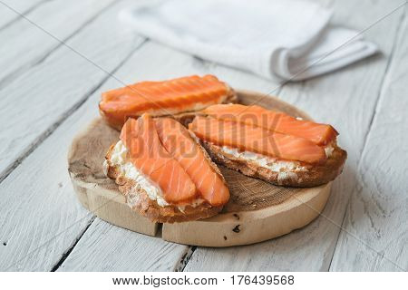 Sandwiches with smoked salmon and cream-cheese on a white wooden table. White napkin at the background