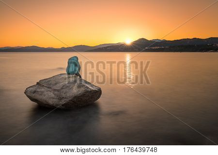 L'ILE ROUSSE, CORSICA - 11th MARCH 2017. Bronze mermaid sculpture called Sirenella di L'Isula Rossa by Gabriel Diana sitting on a rock in the sea at Ile Rousse in the Balagne region of Corsica with the sunrise just appearing over the coast