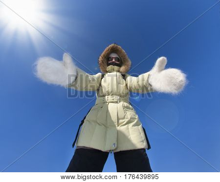 Girl dressed in warm jacket big white woolen mittens stretches out her hands to you. Siberia Russia Cold Frost