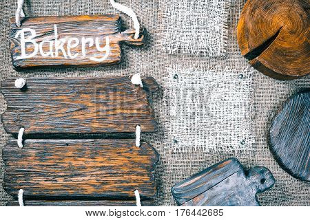 Dark wood boards, wood slice and burlap pieces as frames on burlap background. Wooden signboard with text 'Bakery' as title bar. Rustic style template for food and drink industry