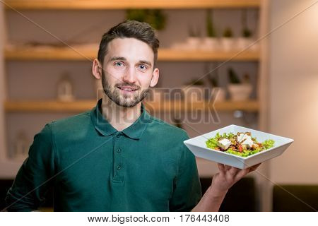 A waiter with a Greek salad on a white plate in his hand. Handsome young waiter at restaurant