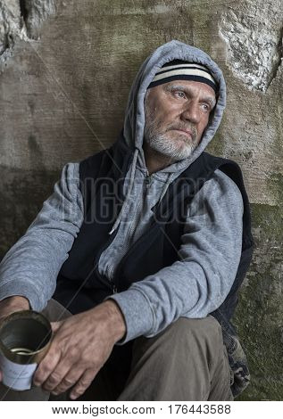 Mature homeless man begging outdoors with a tin