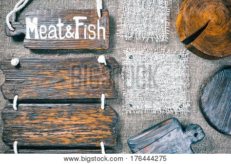 Dark wood boards, wood slice and burlap pieces as frames on burlap background. Wooden signboard with text 'Meat and fish' as title bar. Rustic style template for food and drink industry