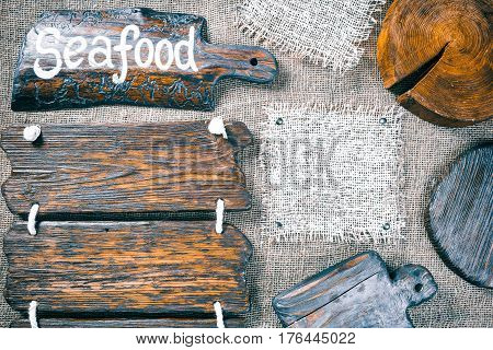 Dark wood boards, wood slice and burlap pieces as frames on burlap background. Wooden signboard with text 'Seafood' as title bar. Rustic style template for food and drink industry