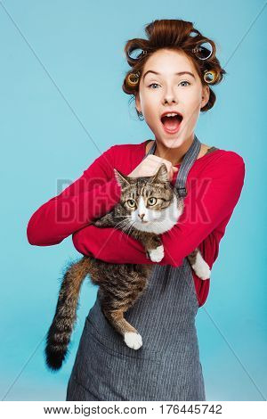 Young charming girl with wide smile on face with cat in hands poses on blue