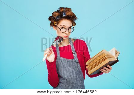 Attractive lady looks for new recipe holding soup ladle in hands while cooking at blue bright kitchen