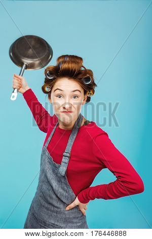 Nice young girl jokes with frying pan in hand while making food for dinner
