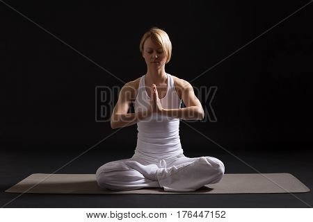 Woman exercising yoga indoor on black background,Lotus position/Padmasana