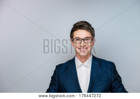 Young and handsome guy in a business suit and glasses smiling at the camera in gray studio