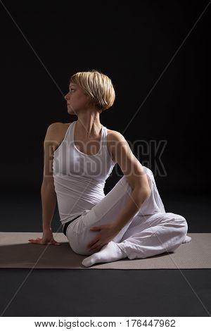 Woman exercising yoga indoor on black background,Half lord of the fishes pose/Ardha Matsyendrasana