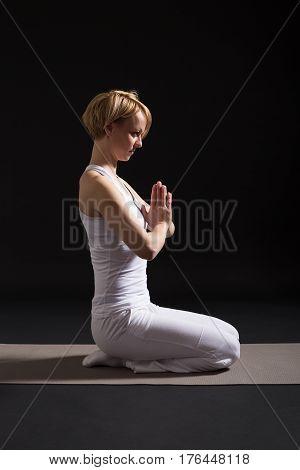 Woman exercising yoga indoor on black background,Half Lotus Position/Padmasana