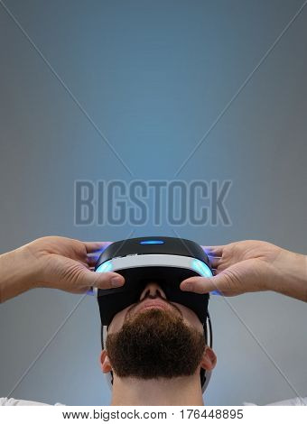 Young man with a beard looks at 3D glasses on the blue background. A man in virtual glasses is looking up above him is a blue glow. Type of shooting from below. Empty copy space for text.