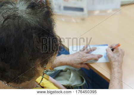 Asian grandma sign her name in deposit for open new account in Thailand bank Photo focus select at gray hair but right are blur for copy space.