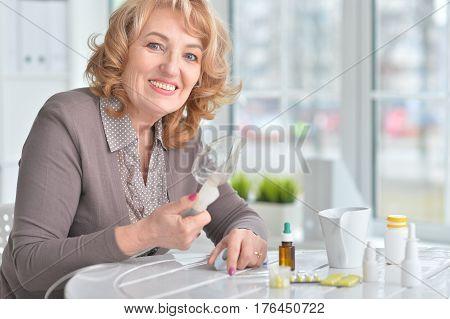 Portrait of an elderly woman doing inhalation