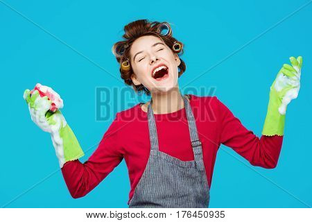Young and pretty housewife sings songs with smile while washing windows in green gloves