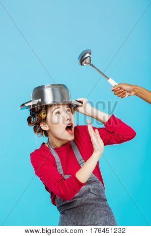 Nice funny girl hides under saucepan from hand holding big ladle