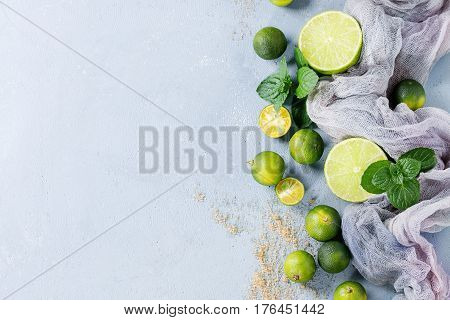 Ingredients for mojito cocktail, whole, sliced lime and mini limes, mint leaves, brown crystal sugar over gray stone texture background with gauze textile. Top view, space
