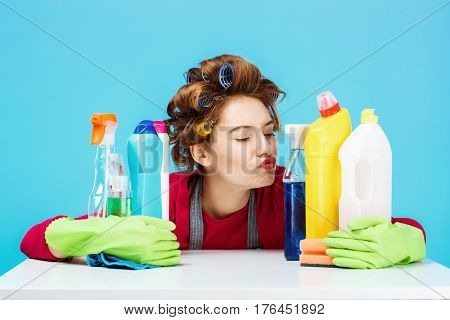 Nice young girl sits behind table with cleaning tools and she holds them in green gloves