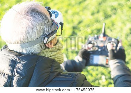 Senior man wearing virtual reality goggles headset with a remote control in his hands playing with flying drone - First person view - Elderly person gaming videogames through vr glasses