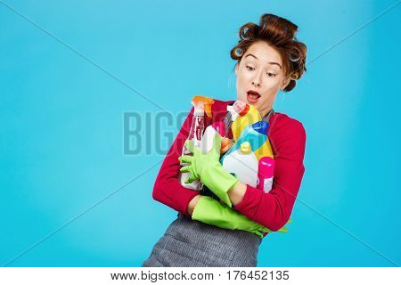 Young nand cheerful housewife in pink and grey outfit with green rubber gloves holds cleaning tools