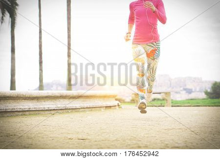 Athletic young woman running outdoor in sunrise light - Sportswoman jogging on a rural road with city in the background - Sports healthy and lifestyle concept