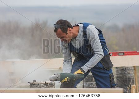 Portrait of builder working with circular saw outdoors, sawdust flying around, telephoto shot