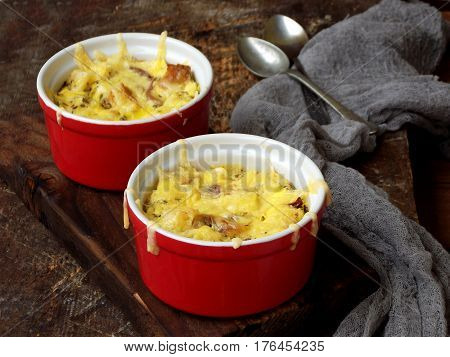Casserole From Eggs, Bacon, Dried Tomatoes And Cheese In Red Ramekin On A Wooden Background